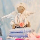 Λίγη συνεδρίαση κουκλών αγγέλου σε ένα μαξιλάρι βαλεντίνος ημέρας s Χέρι παιχνιδιών παιδιών ` s - που γίνεται Στοκ Φωτογραφίες