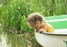 Λίγη συνεδρίαση παιδιών στη βάρκα από μια λίμνη τη θερινή ημέρα Στοκ Εικόνες