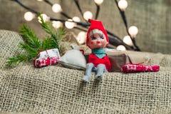 Λίγη συνεδρίαση στοιχειών αρωγών Santa με τις διακοπές Χριστουγέννων παρούσες Στοκ εικόνα με δικαίωμα ελεύθερης χρήσης