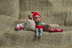Λίγη συνεδρίαση στοιχειών αρωγών Santa με τις διακοπές Χριστουγέννων παρούσες Στοκ Εικόνες