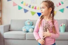 Λίγη χαριτωμένη κοριτσιών Πάσχας εορτασμού στο σπίτι ιτιά εκμετάλλευσης έννοιας μόνιμη που φαίνεται έξω το παράθυρο Στοκ φωτογραφία με δικαίωμα ελεύθερης χρήσης