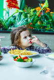 Λίγη χαριτωμένη συνεδρίαση κοριτσιών σε ένα εστιατόριο και κατανάλωση των τηγανιτών πατατών Στοκ εικόνες με δικαίωμα ελεύθερης χρήσης