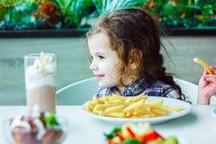 Λίγη χαριτωμένη συνεδρίαση κοριτσιών σε ένα εστιατόριο και κατανάλωση των τηγανιτών πατατών Στοκ φωτογραφία με δικαίωμα ελεύθερης χρήσης