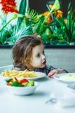 Λίγη χαριτωμένη συνεδρίαση κοριτσιών σε ένα εστιατόριο και κατανάλωση των τηγανιτών πατατών Στοκ φωτογραφίες με δικαίωμα ελεύθερης χρήσης