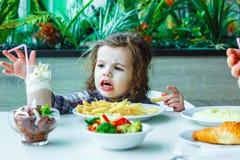 Λίγη χαριτωμένη συνεδρίαση κοριτσιών σε ένα εστιατόριο και κατανάλωση των τηγανιτών πατατών Στοκ εικόνα με δικαίωμα ελεύθερης χρήσης
