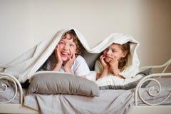 Λίγοι αδελφός και αδελφή έκαναν ένα παιχνίδι στο κρεβάτι στην κρεβατοκάμαρα Στοκ Εικόνα