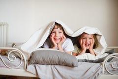 Λίγοι αδελφός και αδελφή έκαναν ένα παιχνίδι στο κρεβάτι στην κρεβατοκάμαρα Στοκ Φωτογραφία