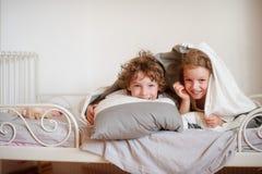 Λίγοι αδελφός και αδελφή έκαναν ένα παιχνίδι στο κρεβάτι στην κρεβατοκάμαρα Στοκ εικόνα με δικαίωμα ελεύθερης χρήσης