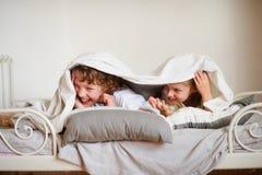 Λίγοι αδελφός και αδελφή έκαναν ένα παιχνίδι στο κρεβάτι στην κρεβατοκάμαρα Στοκ εικόνες με δικαίωμα ελεύθερης χρήσης