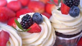 Λίγοι εύγευστα φρούτα cupcake με την άσπρες κτυπημένες κρέμα και τις φέτες των φρέσκων κόκκινων και μαύρων μούρων απόθεμα βίντεο