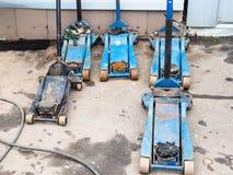 Λίγοι χρησιμοποιημένοι υδραυλικοί γρύλοι για την επισκευή των ροδών στοκ φωτογραφίες