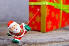 Λίγος Άγιος Βασίλης που τραβά το μεγάλο κιβώτιο δώρων Στοκ Φωτογραφία