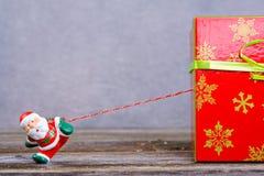 Λίγος Άγιος Βασίλης που τραβά το μεγάλο κιβώτιο δώρων Στοκ Φωτογραφίες