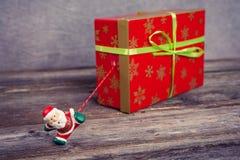 Λίγος Άγιος Βασίλης που τραβά το μεγάλο κιβώτιο δώρων Στοκ Εικόνες