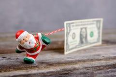 Λίγος Άγιος Βασίλης που τραβά το μεγάλο τραπεζογραμμάτιο Στοκ Φωτογραφίες