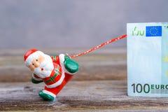 Λίγος Άγιος Βασίλης που τραβά το μεγάλο τραπεζογραμμάτιο Στοκ εικόνες με δικαίωμα ελεύθερης χρήσης