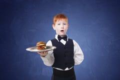 Λίγος έκπληκτος σερβιτόρος αγοριών στέκεται με το εξυπηρετώντας χάμπουργκερ δίσκων Στοκ Εικόνες