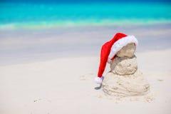 Λίγος αμμώδης χιονάνθρωπος με το κόκκινο καπέλο Santa στο λευκό Στοκ Εικόνα