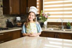 Λίγος αρχιμάγειρας που στέκεται σε μια κουζίνα και ένα χαμόγελο Στοκ φωτογραφία με δικαίωμα ελεύθερης χρήσης