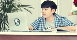 Λίγος ασιατικός προ έφηβος που κάνει την εργασία στο σπίτι με το πρόσωπο χαμόγελου απόθεμα βίντεο