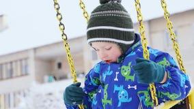 Λίγος καυκάσιος γύρος αγοριών σε μια ταλάντευση στην παιδική χαρά το χειμώνα Στοκ Φωτογραφία