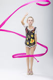 Λίγος καυκάσιος θηλυκός ρυθμικός Gymnast στο επαγγελματικό ανταγωνιστικό κοστούμι που κάνει τις καλλιτεχνικές σπείρες κορδελλών στοκ εικόνα με δικαίωμα ελεύθερης χρήσης