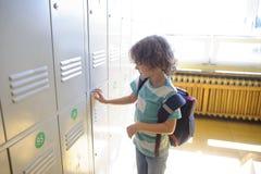 Λίγος μαθητής που στέκεται κοντά στα ντουλάπια στο σχολικό διάδρομο και ανοίγει το drawe του Στοκ φωτογραφία με δικαίωμα ελεύθερης χρήσης