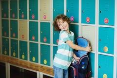 Λίγος μαθητής που στέκεται στην αίθουσα κοντά στα ντουλάπια Στοκ Εικόνες