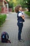 Λίγος μαθητής στέκεται στο σχολικόη ναυπηγείο με μια έκφραση στο πρόσωπό του Στοκ εικόνα με δικαίωμα ελεύθερης χρήσης