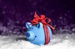 Λίγος μπλε piggy με ένα κόκκινο τόξο στοκ εικόνες