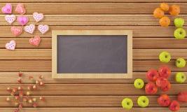 Λίγος πίνακας κιμωλίας που περιβάλλεται από τα φρούτα και τα μπισκότα Στοκ Φωτογραφία