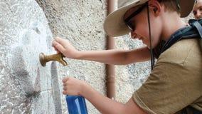 Λίγος ταξιδιώτης που χύνει το νερό στο μπουκάλι από τη δημόσια βρύση πόσιμου νερού απόθεμα βίντεο