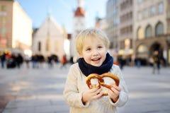 Λίγος τουρίστας που κρατά το παραδοσιακό βαυαρικό ψωμί κάλεσε pretzel στο υπόβαθρο οικοδόμησης Δημαρχείων στο Μόναχο, Γερμανία Στοκ εικόνα με δικαίωμα ελεύθερης χρήσης