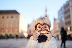 Λίγος τουρίστας που κρατά το παραδοσιακό βαυαρικό ψωμί κάλεσε pretzel στο υπόβαθρο οικοδόμησης Δημαρχείων στο Μόναχο, Γερμανία Στοκ Φωτογραφία