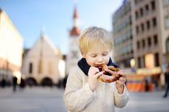 Λίγος τουρίστας που κρατά το παραδοσιακό βαυαρικό ψωμί κάλεσε pretzel στο υπόβαθρο οικοδόμησης Δημαρχείων στο Μόναχο, Γερμανία Στοκ φωτογραφία με δικαίωμα ελεύθερης χρήσης