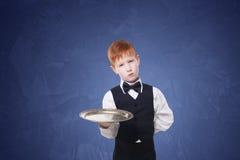 Λίγος λυπημένος σερβιτόρος αγοριών στέκεται με την κενή εξυπηρέτηση δίσκων Στοκ Εικόνες