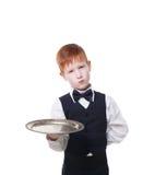 Λίγος λυπημένος σερβιτόρος αγοριών στέκεται με την κενή εξυπηρέτηση δίσκων Στοκ φωτογραφία με δικαίωμα ελεύθερης χρήσης