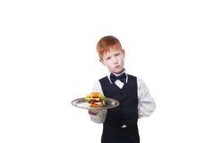 Λίγος λυπημένος σερβιτόρος αγοριών στέκεται με το εξυπηρετώντας χάμπουργκερ δίσκων Στοκ φωτογραφία με δικαίωμα ελεύθερης χρήσης