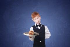 Λίγος λυπημένος σερβιτόρος αγοριών στέκεται με το εξυπηρετώντας χάμπουργκερ δίσκων Στοκ Εικόνα