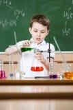 Λίγος χημικός πραγματοποιεί ένα πείραμα στοκ εικόνα με δικαίωμα ελεύθερης χρήσης