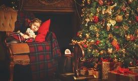 Λίγος ύπνος κοριτσιών παιδιών κοντά σε ένα χριστουγεννιάτικο δέντρο Στοκ Φωτογραφία