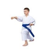 Λίγος karate αθλητής κτυπά το βραχίονα διατρήσεων που απομονώνεται Στοκ Εικόνες