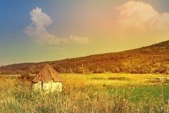 Λίγο άσπρο παλαιό αγροτικό σπίτι που περιβάλλεται ένα ηλιόλουστο τοπίο, θερινό φρέσκο ημερησίως, έναν λόφο που καλύπτονται από με στοκ εικόνα με δικαίωμα ελεύθερης χρήσης