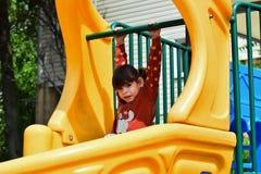Λίγο άτακτο κορίτσι που παίζει στην παιδική χαρά στο πάρκο πόλεων στοκ εικόνα