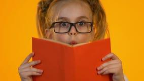 Λίγο έξυπνο παιδί eyeglasses που διαβάζει την εγκυκλοπαίδεια που συγκλονίζεται από τα ενδιαφέροντα γεγονότα απόθεμα βίντεο