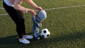 Λίγο αγοράκι και η μητέρα του που παίζουν με τη σφαίρα ποδοσφαίρου στο αγωνιστικό χώρο ποδοσφαίρου απόθεμα βίντεο