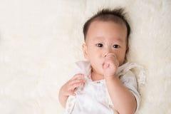 Λίγο αγοράκι 7 μήνες που απορροφούν το δάχτυλο αντίχειρών του στο στόμα Στοκ Εικόνες