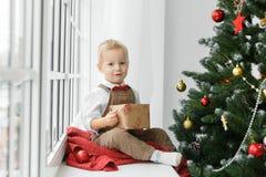 Λίγο αγοράκι με το παρόν στα χέρια του που κάθονται κοντά στο χριστουγεννιάτικο δέντρο και που εξετάζουν τη κάμερα Στοκ εικόνες με δικαίωμα ελεύθερης χρήσης