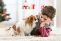 Λίγο αγοράκι με το σκυλί που βρίσκεται στο πάτωμα στο χριστουγεννιάτικο δέντρο Στοκ Εικόνες