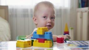 Λίγο αγοράκι που παίζει με τους ζωηρόχρωμους μικρούς φραγμούς ενός κατασκευαστή στο δωμάτιο στο πάτωμα Παιχνίδι παιδιών με χρωματ φιλμ μικρού μήκους